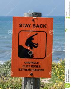 unstable-cliffs-warning-sign-unstable-cliffs-warning-sign-wooden-post-over-cliff-near-ocean-side-102184286